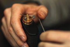 Υπηρεσία μεταπωλήσεων Vape του ηλεκτρονικού τσιγάρου Τα αρσενικά χέρια ρυθμίζουν τις σπείρες ε -ε-cig Προσωπικός ψεκαστήρας στοκ φωτογραφία με δικαίωμα ελεύθερης χρήσης