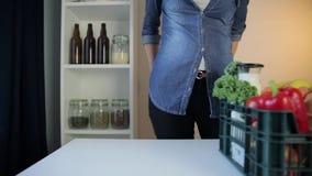 Υπηρεσία παράδοσης τροφίμων - γυναίκα με το κιβώτιο παντοπωλείων στο γκρίζο υπόβαθρο απόθεμα βίντεο