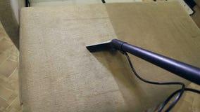 Υπηρεσία που καθαρίζει το βρώμικους καναπέ και τις καρέκλες με το ειδικό εργαλείο απόθεμα βίντεο