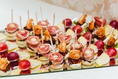 Υπηρεσίες τομέα εστιάσεως Δίσκος γυαλιού με τα πρόχειρα φαγητά με brie, το σταφύλι, το μπέϊκον, και τις γαρίδες σε ένα εστιατόριο Στοκ Φωτογραφίες