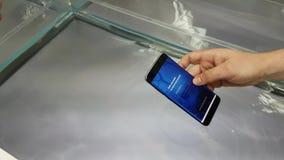 Υποβρύχια επίδειξη ενός νέου smartphone γαλαξιών S8 στο κατάστημα εμπορικών σημάτων της Samsung απόθεμα βίντεο