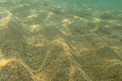 Υποβρύχια φωτογραφία, πυθμένας της θάλασσας στα ρηχά νερά, ήλιος που λάμπουν, ελαφριά διάθλαση στους αμμόλοφους άμμου αφηρημένο ν στοκ εικόνα