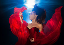Υποβρύχιο όμορφο νέο κορίτσι φωτογραφιών με τη σκοτεινή μακρυμάλλη φθορά Στοκ εικόνες με δικαίωμα ελεύθερης χρήσης