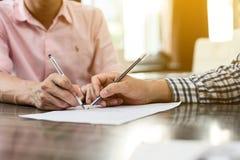 Υπογραφή μιας σύμβασης ακίνητων περιουσιών μεταξύ του αγοραστή και του μεσίτη Στοκ Εικόνα