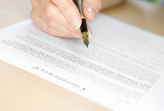 Υπογραφή μιας σύμβασης με την πέννα πηγών Στοκ Φωτογραφία