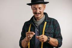 Υποδηματοποιός στη μοντέρνη ταινία καπέλων και μέτρου που περνά κλωστή στη βελόνα που απομονώνεται στο στούντιο στοκ φωτογραφία