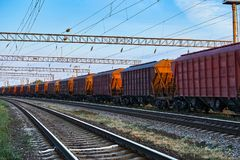 Υποδομή σιδηροδρόμου κατά τη διάρκεια του όμορφου ηλιοβασιλέματος και του ζωηρόχρωμου ουρανού, της αυτοκινητάμαξας για το ξηρό φο Στοκ Εικόνα