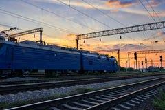 Υποδομή σιδηροδρόμου κατά τη διάρκεια του όμορφου ηλιοβασιλέματος και του ζωηρόχρωμου ουρανού, των τραίνων και των βαγονιών εμπορ Στοκ Εικόνες