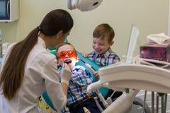 Υποδοχή στην οδοντιατρική Ένα χαμογελώντας μικρό παιδί βάζει στον καναπέ στα προστατευτικά γυαλιά στοκ εικόνες