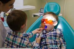 Υποδοχή στην οδοντιατρική Δύο αγόρια στο γραφείο Ο οδοντίατρος που εργάζεται με το λαμπτήρα των οδηγήσεων στοκ φωτογραφία