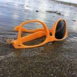 Υποκείμενα σε ντάμπινγκ σπασμένα γυαλιά ηλίου στην παραλία Στοκ εικόνα με δικαίωμα ελεύθερης χρήσης