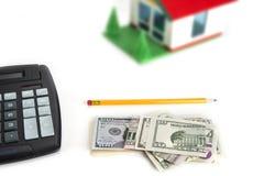 Υπολογισμός χρημάτων αποταμίευσης για ένα σπίτι γίνοντη σπίτι υποθήκη δολαρίων έννοιας 100 λογαριασμών έξω στοκ φωτογραφία