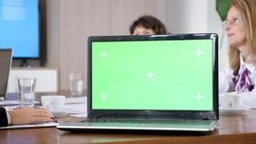 Υπολογιστής με την πράσινη χλεύη χρώματος οθόνης επάνω σε έναν πίνακα στη αίθουσα συνδιαλέξεων απόθεμα βίντεο