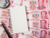 Υπολογιστής, σημειωματάριο και μολύβι στο κινεζικό νόμισμα τραπεζογραμματίων Yuan Στοκ Φωτογραφίες