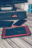 Υπολογιστής ταμπλετών με το σπασμένο γυαλί, που βρίσκεται στον υπολογιστή γραφείου με το τηλέφωνο και άλλες συσκευές στοκ φωτογραφία με δικαίωμα ελεύθερης χρήσης