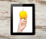 Υπολογιστής ταμπλετών με το χέρι και το κίτρινο μήλο Στοκ εικόνα με δικαίωμα ελεύθερης χρήσης