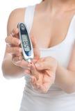 Υπομονετική γυναίκα διαβήτη που μετρά τη εξέταση αίματος επιπέδων γλυκόζης στοκ εικόνα