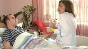 Υπομονετική εξέταση στο νοσοκομείο Γυναίκα και άνδρας γιατρών που βρίσκονται στο κρεβάτι απόθεμα βίντεο