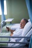 Υπομονετική τηλεόραση προσοχής στο κρεβάτι στοκ φωτογραφίες με δικαίωμα ελεύθερης χρήσης