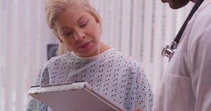 Υπομονετικός λέγοντας γιατρός γυναικών για την ιστορία υγείας της στοκ φωτογραφία