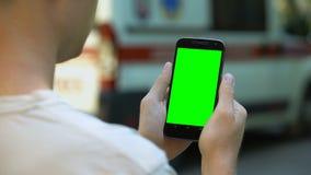 Υπομονετικό χρησιμοποιώντας κινητό τηλέφωνο για να διαβάσει τα αποτελέσματα της δοκιμής, ασθενοφόρο για το υπόβαθρο, κινηματογράφ απόθεμα βίντεο