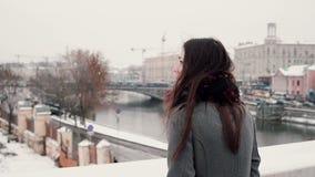 υποστηρίξτε την όψη Η ελκυστική νέα στάση κοριτσιών brunette στη γέφυρα και εξετάζει τη χιονισμένη χειμερινή πόλη φιλμ μικρού μήκους