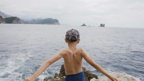 υποστηρίξτε την όψη Μικρό παιδί που αυξάνει τα χέρια του επάνω υψηλά πάνω από τον απότομο βράχο επάνω από τη θάλασσα στην όμορφου απόθεμα βίντεο