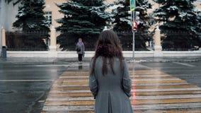 υποστηρίξτε την όψη Το λυπημένο νέο κορίτσι brunette περιμένει το πράσινο φως για να διασχίσει το δρόμο σε μια χειμερινή χιονισμέ απόθεμα βίντεο