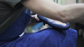 Υποδηματοποιός που εφαρμόζει την κόλλα σε ένα μπλε πέλμα παπουτσιών με μια βούρτσα απόθεμα βίντεο