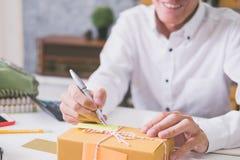 Υπολογισμός του κόστους των ταχυδρομικών τελών μιας μικρής συσκευασίας στοκ εικόνες