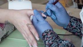 Υπολογισμός του UV καρφιού στίλβωση πηκτωμάτων των επαγγελματικών οδηγήσεων καρφιών στο σαλόνι closeup φιλμ μικρού μήκους