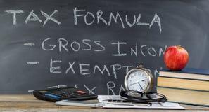 Υπολογιστής γραφείου και πίνακας κιμωλίας για την εκμάθηση πώς να κάνει τους φόρους εισοδήματος στο CL Στοκ φωτογραφία με δικαίωμα ελεύθερης χρήσης