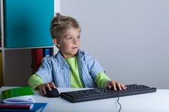 Υπολογιστής παιχνιδιού αγοριών αντί της εκμάθησης Στοκ φωτογραφία με δικαίωμα ελεύθερης χρήσης