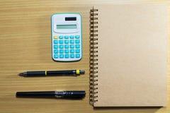 Υπολογιστής, στυλός, μολύβι και σημειωματάριο στον ξύλινο πίνακα Τοπ όψη Στοκ Εικόνες