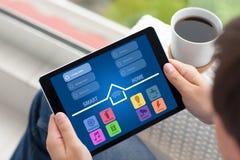 Υπολογιστής ταμπλετών εκμετάλλευσης ατόμων με app το έξυπνο σπίτι στην οθόνη Στοκ Εικόνες