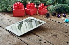 Υπολογιστής ταμπλετών με τα δώρα Χριστουγέννων στην ξύλινη επιτραπέζια κινηματογράφηση σε πρώτο πλάνο Στοκ εικόνα με δικαίωμα ελεύθερης χρήσης
