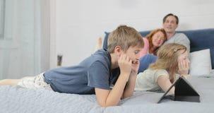 Υπολογιστής ταμπλετών χρήσης κρεβατιών γιων που βρίσκεται στους γονείς πέρα από την ευτυχή χαμογελώντας οικογένεια μαζί στο πρωί απόθεμα βίντεο