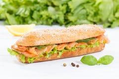 Υπο- baguette σιταριών σάντουιτς ολόκληρο με τα καπνισμένα ψάρια σολομών στο wo στοκ φωτογραφία με δικαίωμα ελεύθερης χρήσης