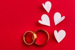 Υπόβαθρο αγάπης - δύο χρυσά γαμήλια δαχτυλίδια και χειροποίητες καρδιές de Στοκ Εικόνα