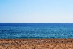 Υπόβαθρο, αμμοχάλικο, μπλε ουρανός και θάλασσα στοκ εικόνες