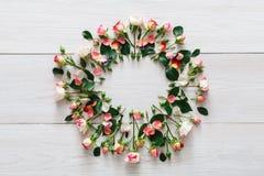 Υπόβαθρο ανθοπωλείων, κύκλος τριαντάφυλλων στο άσπρο ξύλο στοκ εικόνα