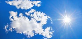 Υπόβαθρο από το μπλε ουρανό με τα άσπρους σύννεφα και τον ήλιο Στοκ Εικόνα