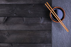 Υπόβαθρο για τα σούσια Σάλτσα σόγιας, chopsticks στη μαύρη πέτρα Τοπ άποψη με το διάστημα αντιγράφων στοκ φωτογραφία με δικαίωμα ελεύθερης χρήσης