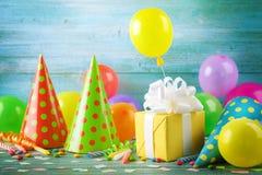 Υπόβαθρο γιορτής γενεθλίων με το κιβώτιο δώρων, τα ζωηρόχρωμα μπαλόνια, το κομφετί, καρναβάλι ΚΑΠ και την ταινία Προμήθειες διακο στοκ φωτογραφίες