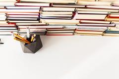 Υπόβαθρο, γυαλιά, στυλοί και μολύβια βιβλίων στον άσπρο ξύλινο πίνακα στοκ εικόνες
