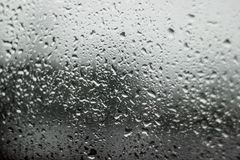Υπόβαθρο εικόνας θαμπάδων της πτώσης νερού στο παράθυρο αυτοκινήτων και το υπόβαθρο οδών Στοκ Εικόνες