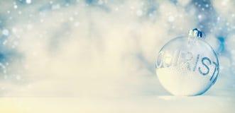 Υπόβαθρο εμβλημάτων Χριστουγέννων με τη σφαίρα γυαλιού στο μπλε χειμερινό bokeh υπόβαθρο Στοκ φωτογραφία με δικαίωμα ελεύθερης χρήσης