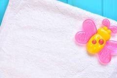 Υπόβαθρο εξαρτημάτων μωρών Ρόδινη πεταλούδα teether σε μια άσπρη πετσέτα στοκ εικόνες με δικαίωμα ελεύθερης χρήσης