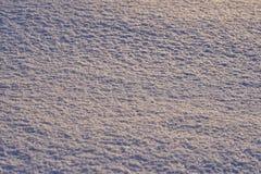 Υπόβαθρο - επιφάνεια πάγου του χιονιού που φωτίζεται φυσικό από τις ακτίνες του ήλιου βραδιού Στοκ Εικόνα