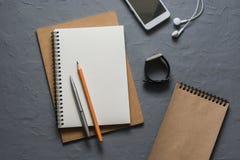 Υπόβαθρο επιχειρήσεων ή εκπαίδευσης Σημειωματάρια, τηλέφωνο, ακουστικά, μολύβια, μάνδρες, ρολόι στο γκρίζο υπόβαθρο, τοπ άποψη κε Στοκ Εικόνες